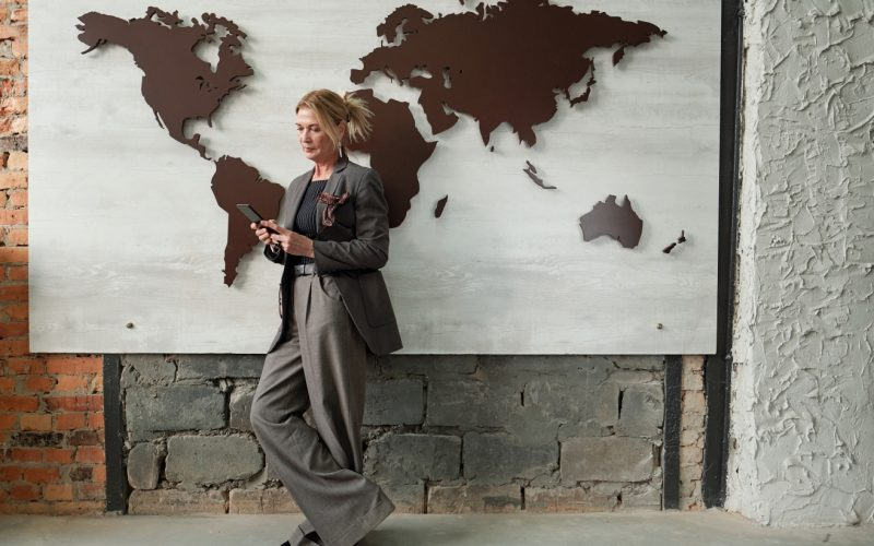 Serious mature female manager on international relationship standing against wall with map design and answering messages on phone